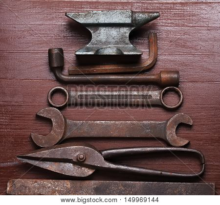 Old rusty rugged anvil and other blacksmith tools on brown natural wooden background in a shape of christmas tree. Flat lay top view.