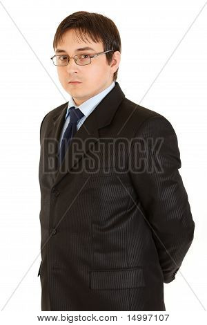 Serious young businessman with eyeglasses holding hands behind his back isolated on white