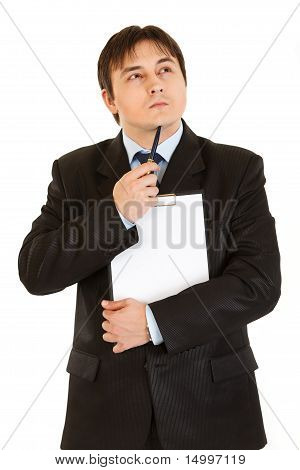 Pensive businessman with clipboard holding pen near his chin isolated on white