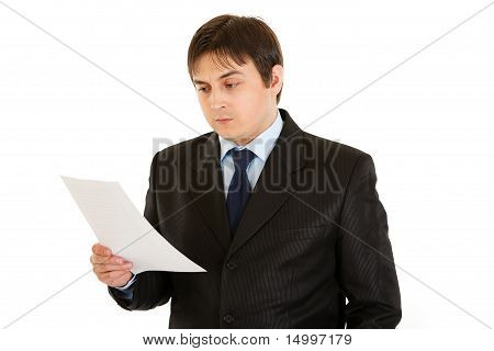 Concentrated businessman checking document isolated on white