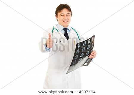 Smiling medical doctor holding tomography and showing thumbs up gesture isolated on white