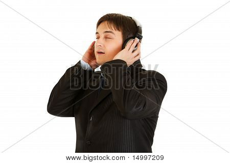 Young businessman in earphone enjoys listening music isolated on white