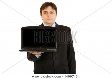Young businessman holding laptop with blank screen isolated on white