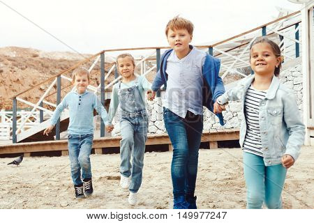 Group of fashion children wearing denim clothing running on the sea shore. Autumn casual outfit in blue and navy color. 7-8 years old models.