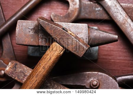 Old rusty rugged anvil hammer other blacksmith tools on brown natural wooden background. Flat lay top view.