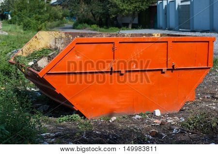 Large orange garbage container standing on the street.