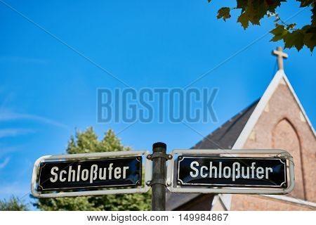 DUESSELDORF, GERMANY - AUGUST 17, 2016: The Schlossufer adress is printed on a double street sign at the Rhine promenade