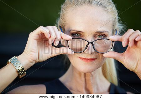 Glad Businesswoman Holding Spectacles