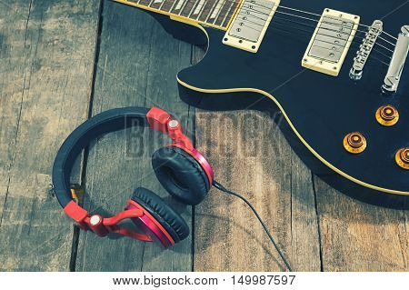 Guitar recording scene. An electric guitar memo pad and a professional grade headphones on a rustic or bare wooden tablevintage effect.