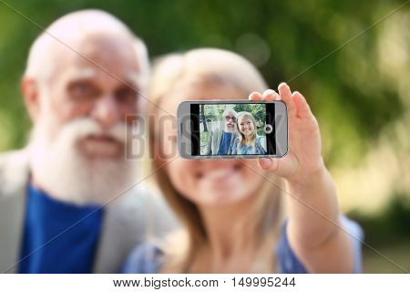Grandfather and granddaughter taking picture on blurred background