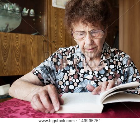 Old woman. Elderly female at home reading Book