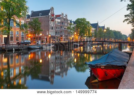 Amsterdam canal Kloveniersburgwal with typical dutch houses, bridge and houseboats during morning blue hour, Holland, Netherlands.