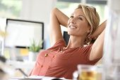 Portrait of beautiful middle-aged woman relaxing in office poster