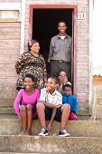 foto of deprivation  - Cheerful black family on the steps infront of their rural house - JPG
