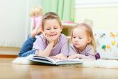 stock photo of girl reading book  - Brother and his little sister at home reading - JPG