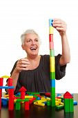 Senior Woman Building Block Tower