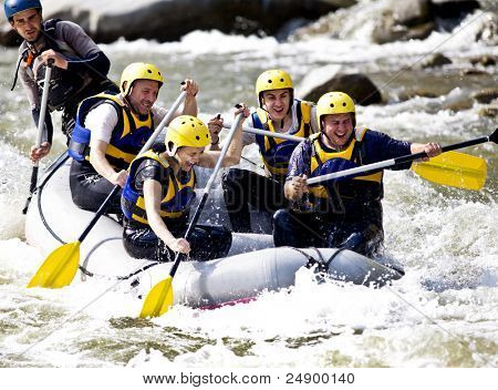 Group of happy people with guide whitewater rafting and rowing on river