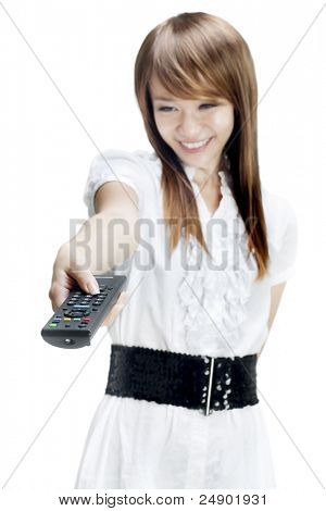 Young woman holds out a remote control to change television stations.