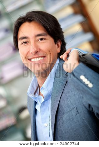 Man shopping at a clothing store and smiling