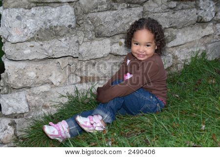 Smiling Girl By A Rock Wall