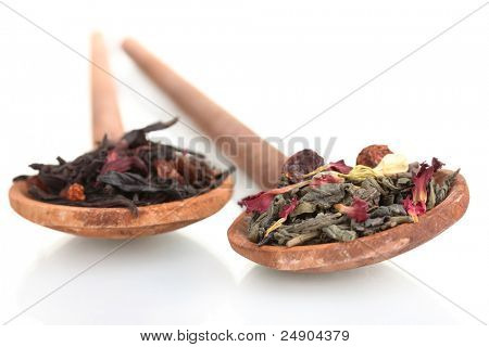 Green and black dry tea leaves in woooden spoons isolated on white