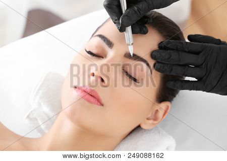 poster of Young woman undergoing procedure of eyebrow permanent makeup in beauty salon