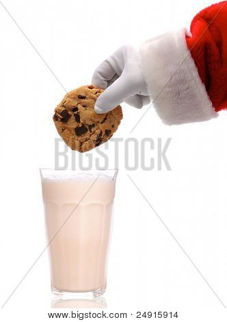 Santa Claus about to dunk a chocolate chip cookie into a glass of milk over a white background