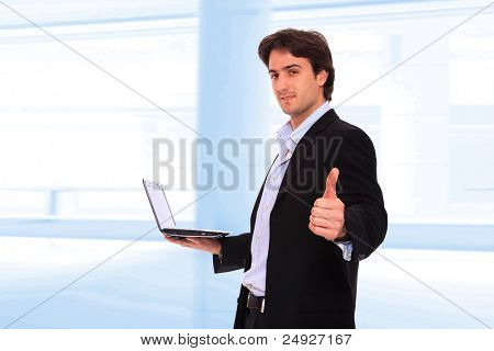 Closeup of a young smiling business man standing and holding a laptop  in a light and mordern business environement