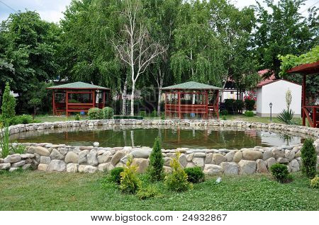 Wooden Arbours Around A Beautiful Pond With Stone Trim