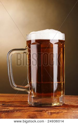 beer mug on wooden table on brown background