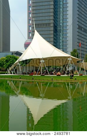 Reflection Of Skyscrapers And Tent Over Lake