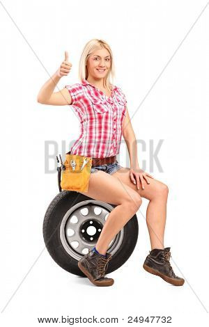A smiling mechanic female giving a thumb up seated on a spare tire isolated on white background