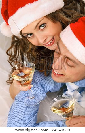 Young lovely couple in Santa hats holding the glasses of martini and clinking glasses.