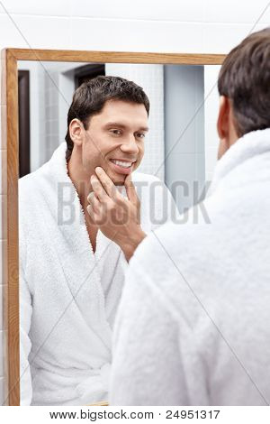 The young man looks in the mirror in the bathroom