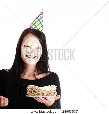 Funny portrait of beautiful young caucasian woman with birthday cake on her face, isolated on white background