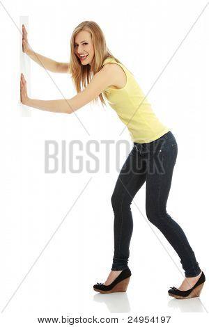 Frau schob etwas imaginären isoliert über eine weiße Hintergrund (weiße Wand über ihre Hände)