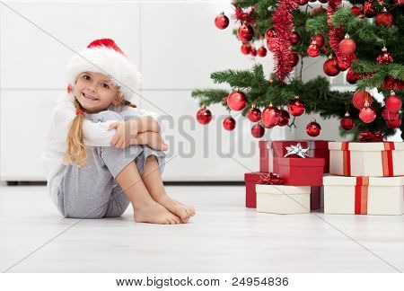 I have lots of presents - smiling little girl in front of the christmas tree