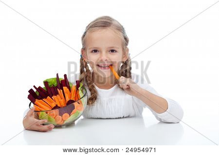 Little girl munching on a carrot stick holding bowl of vegetables