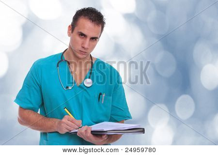 Caucasian mid adult male doctor over bokeh blue background taking notes