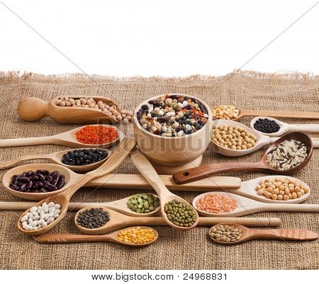 Mix from different beans, legumes, peas, lentils in spoon on the sackcloth