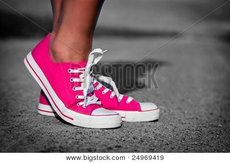 Pink sneakers on girl, young woman legs, outdoors in black and white