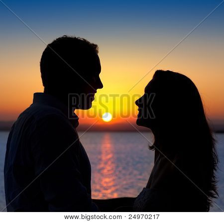 couple in love back light silhouette at lake orange sunset