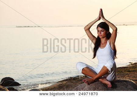 Young woman practicing yoga  near the ocean