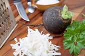 pic of grated radish  - Black radish rub on a small grater for salad preparation