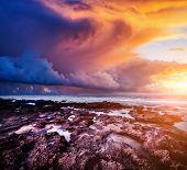 Epic sunset with dark overcast sky. Climate change. Location Island Sicilia, cape Passero, Italy, Eu poster