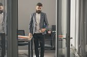 Confident Man In Casual Suit At Working Place. Bearded Man Look Out Room Door. Businessman In Modern poster