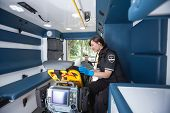 stock photo of triage  - EMT worker listening to heart rate of patient - JPG