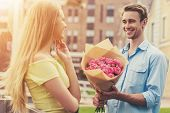 Handsome Young Man Gives Flowers To Cute Girl.. Beautiful Romantic Couple. Bouquet Of Pink Roses. Wo poster