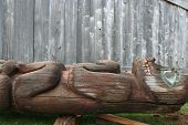 stock photo of tlingit  - Old Tlingit Alaska Native totem pole lies on ground next to wall of tribal house on historic Shakes Island at Wrangell - JPG