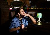 Guy Sitting At Bar Counter And Drinks Beer. Men With Glasses Of Beer Near Bar Counter. Service And C poster